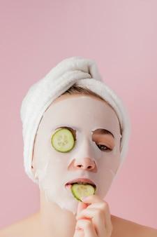 Hermosa joven está aplicando una máscara de tejido cosmético en una cara con pepino