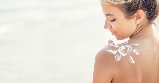 Hermosa joven aplicando protector solar en su hombro en la playa.