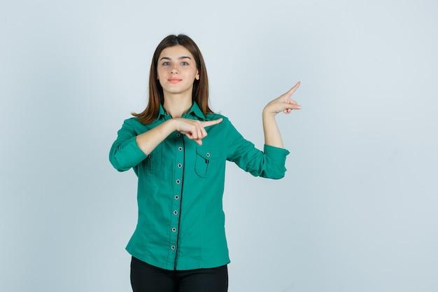 Hermosa joven apuntando a la derecha en camisa verde y mirando confiada. vista frontal.