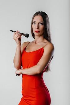 Una hermosa joven artista de maquillaje posa con borlas sobre un fondo blanco en el estudio. maquillaje