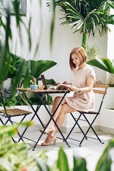 Hermosa joven asiática bebiendo por la mañana en el café y llenando el planificador con ideas