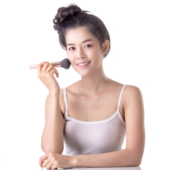 Hermosa joven asiática con cepillo suave y cosméticos en su propia cara.