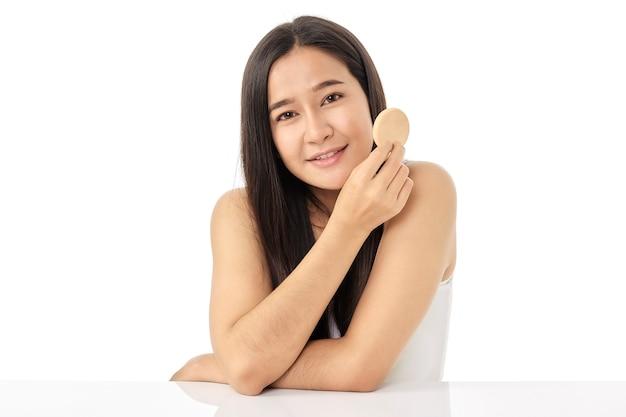 Hermosa joven asiática limpiando la cara de belleza, usando almohadillas de algodón, loción limpiadora y tóner facial para desmaquillar. una hermosa niña tiene una bonita piel facial. concepto de cuidado de la piel.