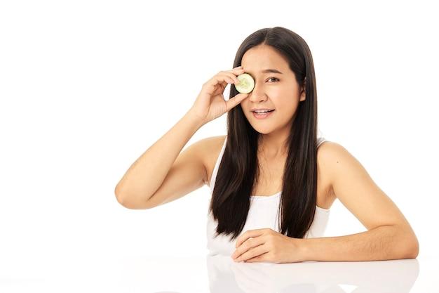 Hermosa joven asiática limpiando la cara de belleza, usando loción limpiadora de rodajas de pepino y tónico facial para desmaquillar. una hermosa niña tiene una bonita piel facial.