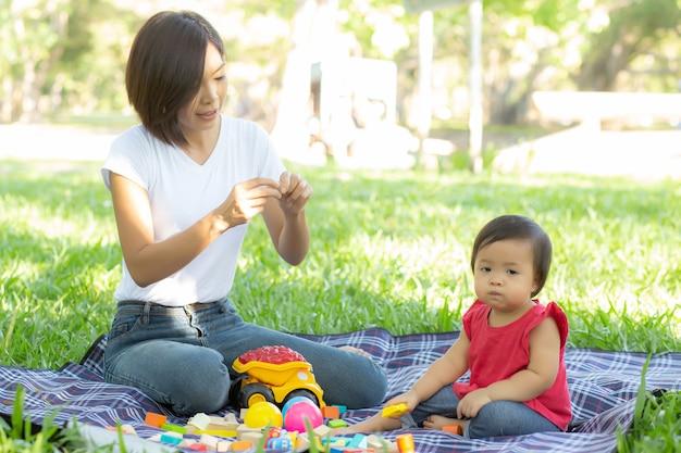 Hermosa joven asiática madre e hija jugando bloques de juguete