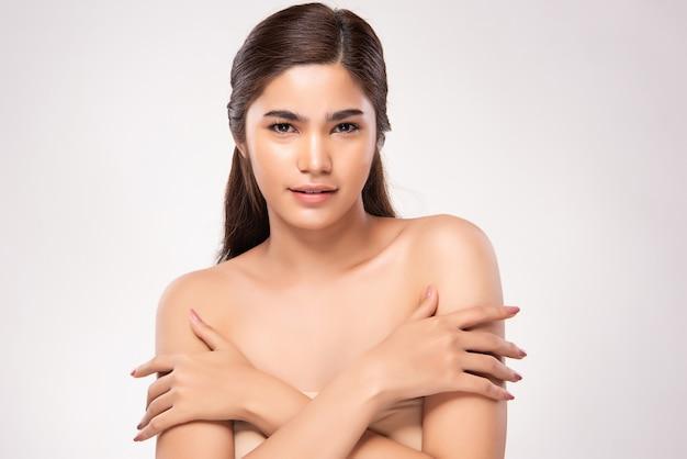 Hermosa joven asiática mano tocando el hombro. piel limpia y fresca, aislada, concepto de belleza cosmetología,