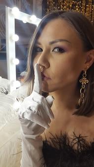 Hermosa joven asiática y mesa de oro junto a un espejo de maquillaje prepárate para la fiesta de getsby