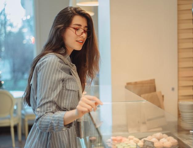 Una hermosa joven asiática con el pelo largo elige un postre en un café junto a la ventana. hermoso interior de panadería cafe