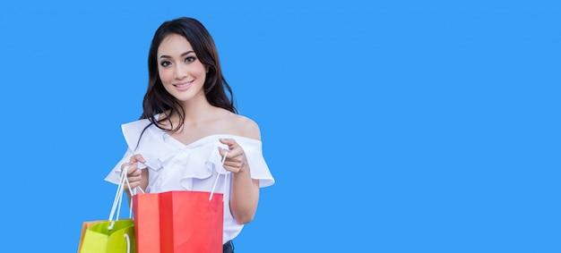 Hermosa joven asiática está de pie sosteniendo bolsas de la compra. ella sonríe felicidad en el centro comercial sobre fondo azul