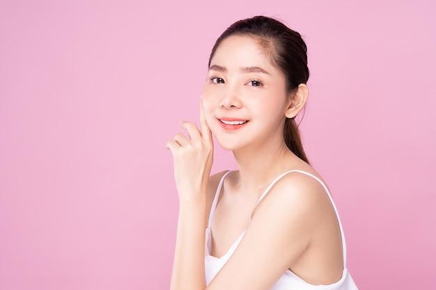Hermosa joven asiática con piel blanca limpia y fresca tocando su propio rostro suavemente en pose de belleza.