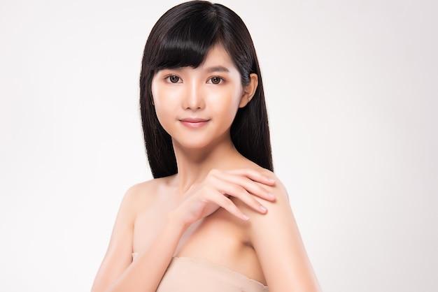 Hermosa joven asiática con piel limpia y fresca. cuidado facial, tratamiento facial, en pared blanca, concepto de belleza y cosmética