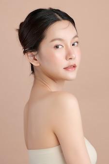 Hermosa joven asiática con piel limpia y fresca sobre fondo beige, cuidado facial, tratamiento facial, cosmetología, belleza y spa, retrato de mujeres asiáticas.