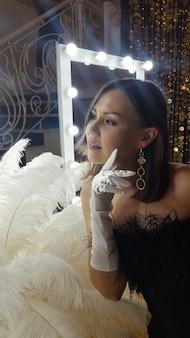 Hermosa joven asiática y plumas de avestruz decorativas en una mesa de oro junto a un espejo de maquillaje