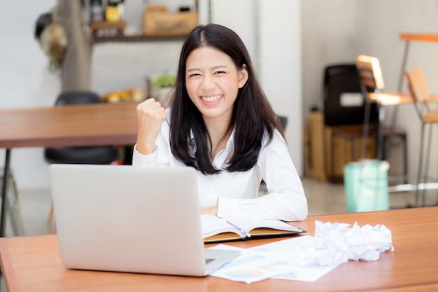 Hermosa joven asiática que trabaja en línea en la computadora portátil
