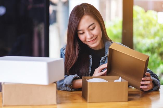 Una hermosa joven asiática recibiendo y abriendo un paquete postal en casa para la entrega y el concepto de compra en línea