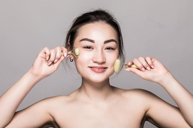 Hermosa joven asiática con un rodillo de cara de jade en su piel perfecta. primer plano de cara de belleza. conceptual de tratamientos faciales con piedras semipreciosas. aislado en gris con espacio de copia