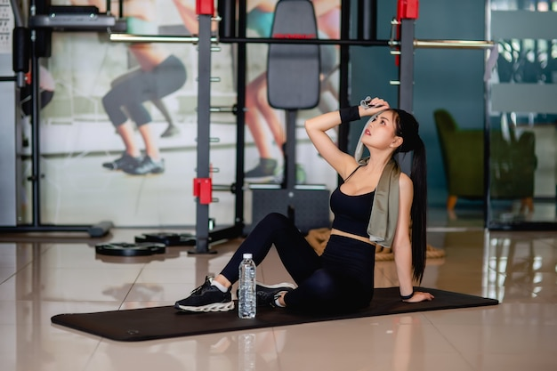 Hermosa joven asiática en ropa deportiva cansada después de hacer ejercicio sentado en la estera de yoga cerca del agua potable y usar una toalla limpiando el sudor en la frente