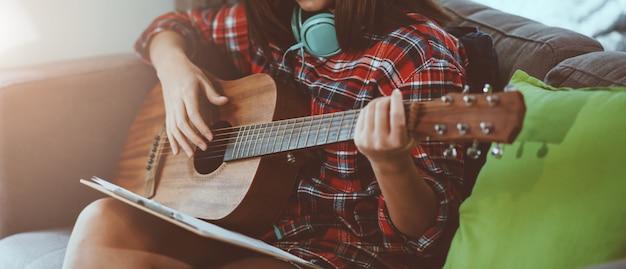 Hermosa joven asiática tocando la guitarra en casa para relajarse