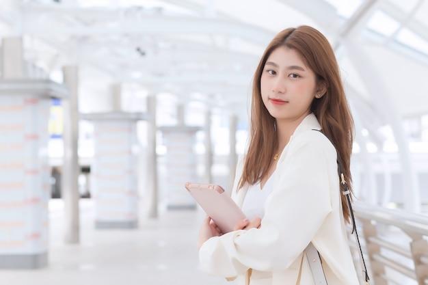 Hermosa joven asiática trabajadora de negocios profesional en traje blanco está al aire libre para conocer a un cliente en la oficina con su tableta de mano con edificios comerciales y ciudad de fondo.