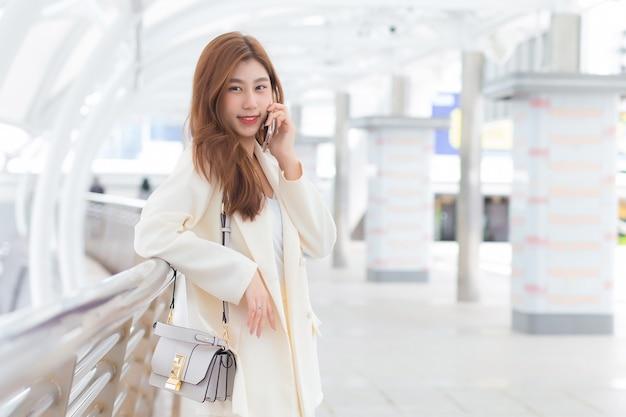 Hermosa joven asiática trabajadora profesional en traje blanco sonríe y sostiene un teléfono inteligente en sus manos en feliz día de trabajo con edificios comerciales y ciudad de fondo.