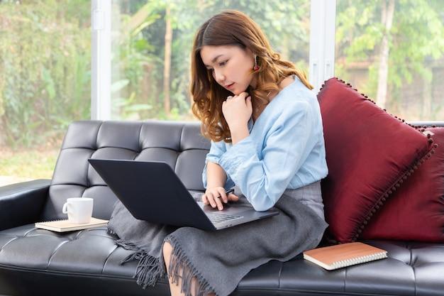 Hermosa joven asiática trabajando en su computadora en su sala de estar en casa