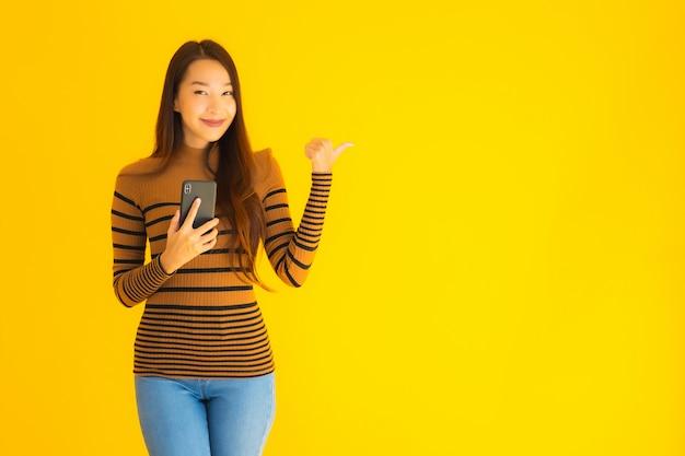 Hermosa joven asiática utiliza teléfono móvil inteligente o teléfono celular con mucha acción en la pared amarilla