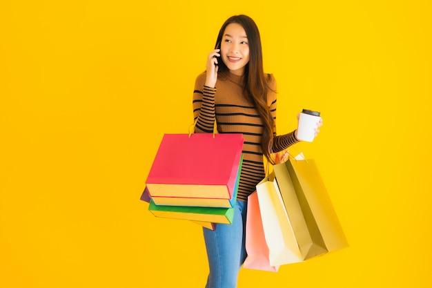 Hermosa joven asiática utiliza teléfono móvil inteligente o teléfono móvil con taza de café y bolsa de compras de color en la pared amarilla