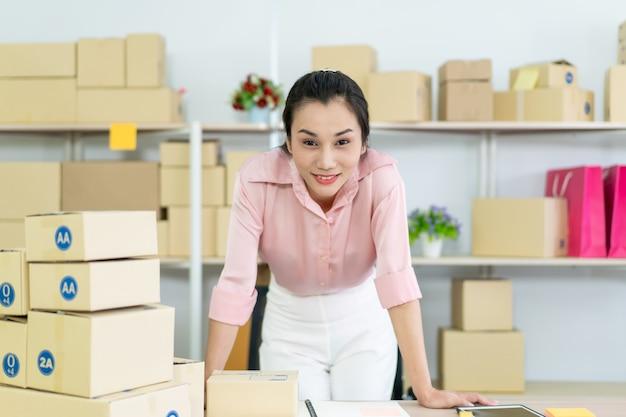 Hermosa joven asiática vendedor en línea de embalaje y comprobación de pedidos entrantes en el almacén