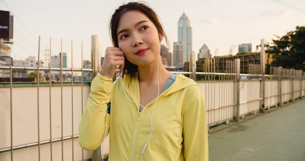 Hermosa joven atleta asiática ejercicios con smartphone para escuchar música mientras se ejecuta en un entorno urbano. chica adolescente coreana vistiendo ropa deportiva en puente de pasarela en la mañana temprano.