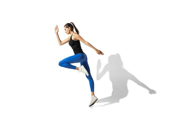 Hermosa joven atleta de estiramiento, entrenamiento en espacios en blanco, retrato con sombras