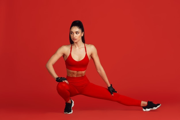 Hermosa joven atleta practicando en pared roja retrato monocromo