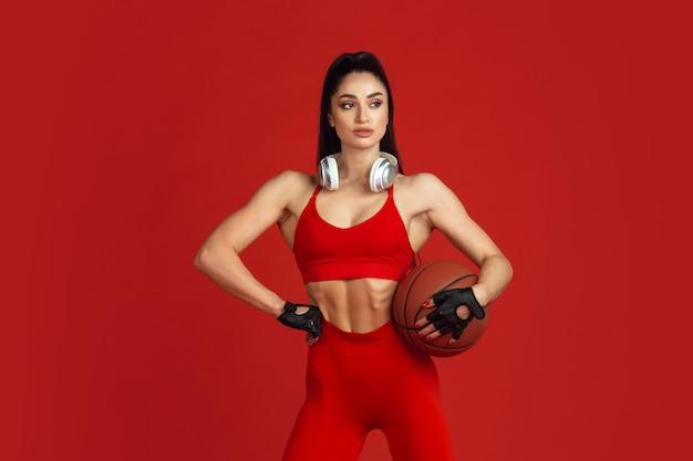 Hermosa joven atleta practicando en rojo