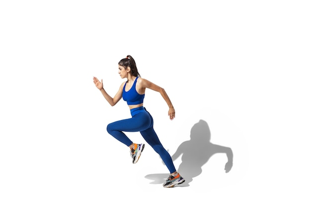 Hermosa joven atleta practicando sobre fondo blanco de estudio, retrato con sombras. modelo de ajuste deportivo en movimiento y acción.