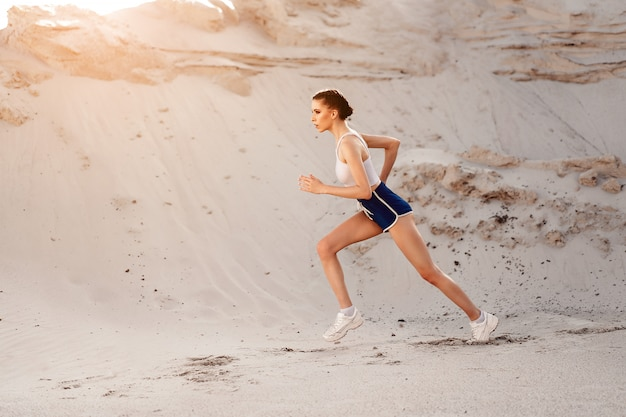Hermosa joven atlética sexy corriendo en la mañana de verano de naturaleza.