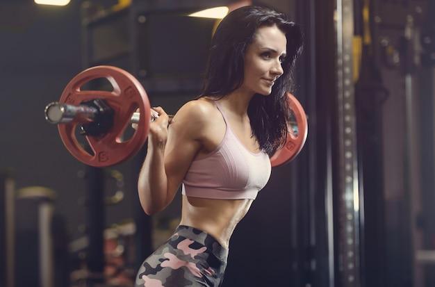 Hermosa joven atlética trabajando en el gimnasio
