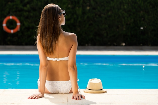 Hermosa, joven, atractiva chica disfrutar en el verano cerca de la piscina.