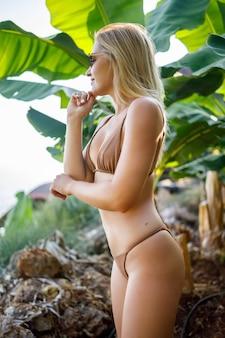 Una hermosa joven atractiva se encuentra cerca de un árbol de plátano, una niña vestida en traje de baño camina sobre una plantación de plátanos, plantas exóticas