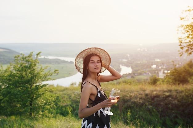 Una hermosa joven atractiva con un vestido elegante y un sombrero de paja bebe vino en la colina en un picnic.