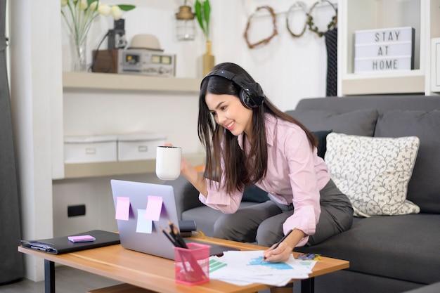 Una hermosa joven con auriculares está haciendo una videoconferencia a través de una computadora en casa durante la pandemia de coronavirus
