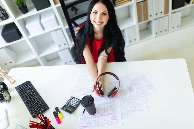 Hermosa joven con auriculares en las manos está sentado en la oficina en la mesa.