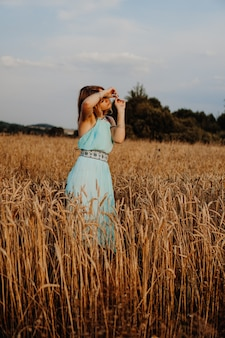 Hermosa joven bailando en el campo al atardecer