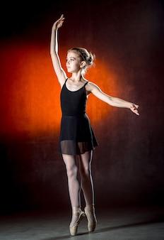 Hermosa joven bailarina está bailando en el estudio en una pared oscura un pequeño bailarín. bailarina de ballet.