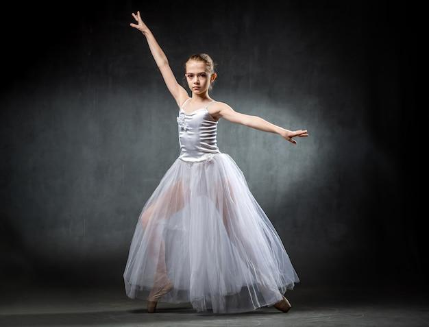 Hermosa joven bailarina está bailando en el estudio sobre un fondo oscuro. una pequeña bailarina bailarina de ballet.