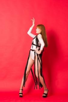 Hermosa joven bailarina posando en un estudio en rojo