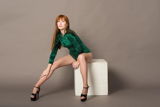 Hermosa joven bailarina posando en un estudio sobre fondo gris