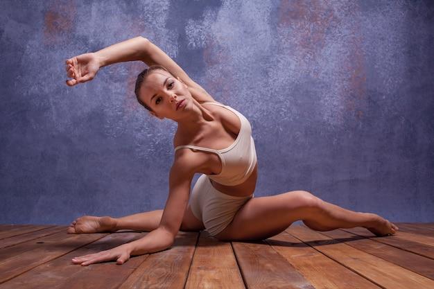 Hermosa joven bailarina en traje de baño beige bailando en estudio lila sobre piso de madera