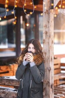 Hermosa joven bebe café en la terraza abierta del café en una noche fresca