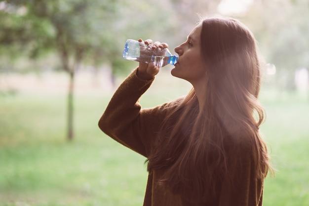 Hermosa joven bebiendo agua de una botella de plástico en la calle en el parque en otoño o invierno