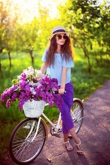 Hermosa joven con bicicleta vintage y flores en la ciudad backgroundd en la luz del sol al aire libre.