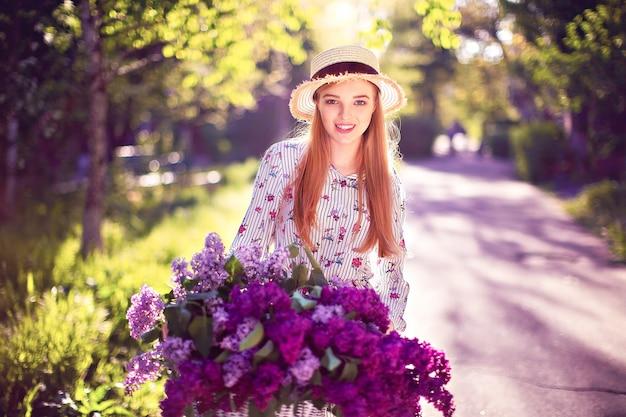 Hermosa joven con bicicleta vintage y flores
